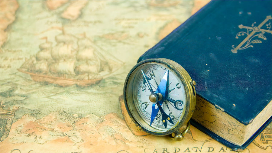 The compass beside a blue book with a cross on the cover. The compass and the book is on top of a navigational map Antique Navigational Compass Direction Compass Travel Exploration Cartography Journey Map South North East West Navigational Geography UHD 4K