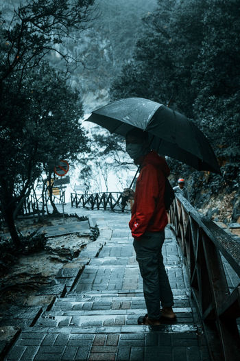 Full length of person standing on wet footpath during monsoon