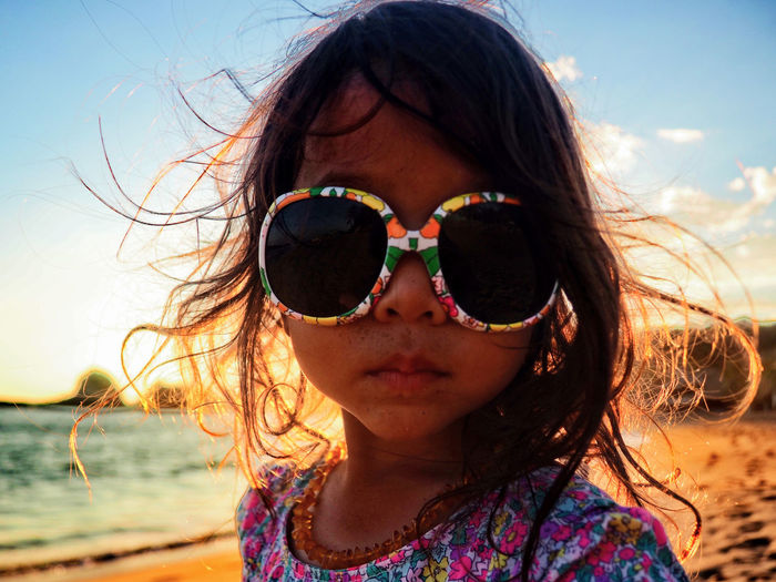 Portrait Of Girl Wearing Sunglasses At Beach Against Sky