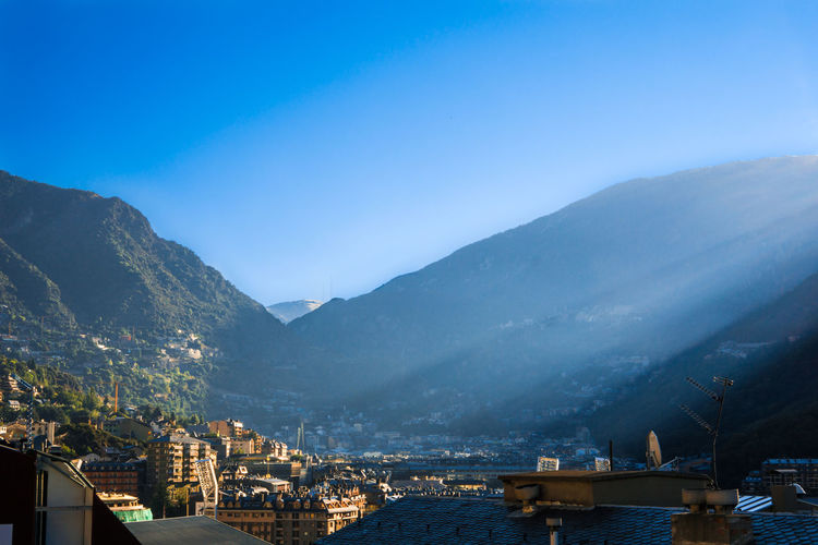 Sunrise over a town in the mountains Architecture Beauty In Nature Blue Building Exterior Built Structure City Cityscape Clear Sky Fog House Housing Settlement Mountain Mountain Range No People Outdoors Residential Building Residential Structure Scenics Sky Sunrise Town Valley Water Wide Shot