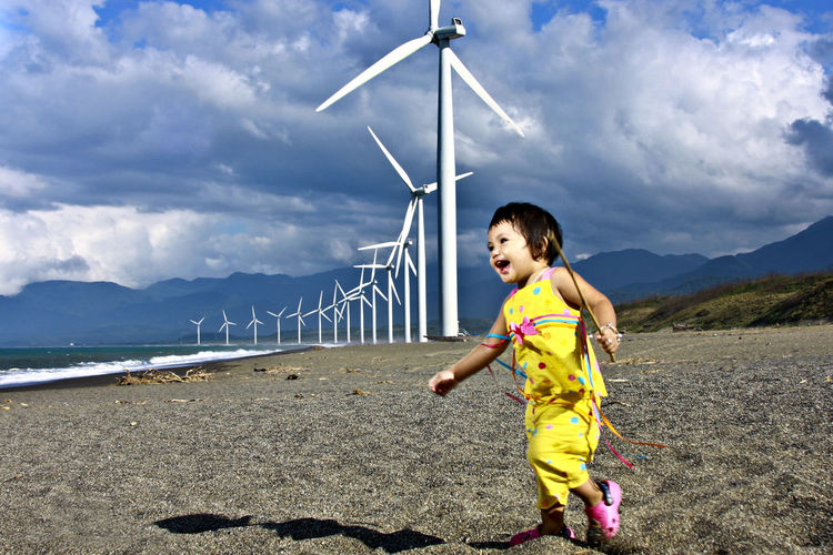Toddler running on sand against wind turbines at beach