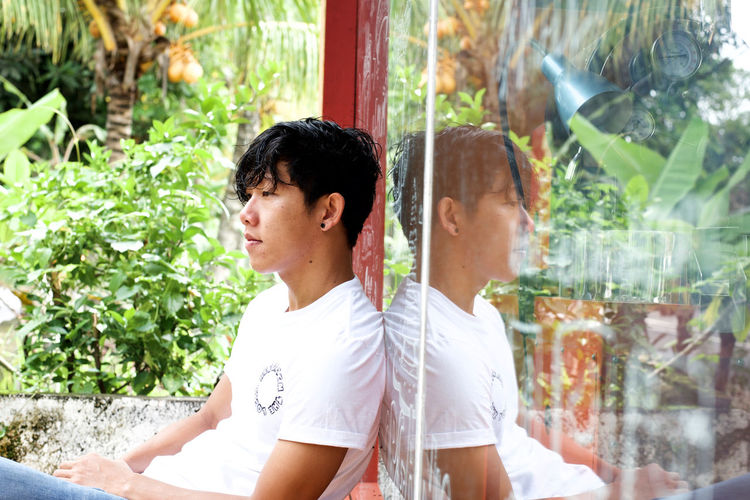Side View Of Thoughtful Young Man Sitting Outdoors
