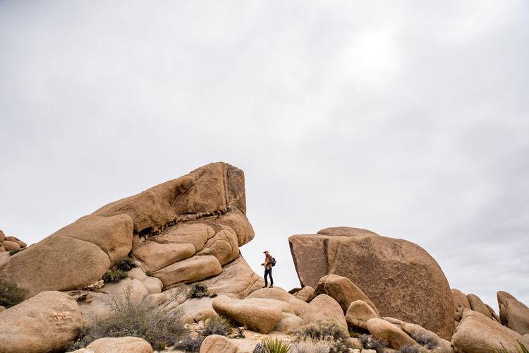 Man rock on rocks against sky