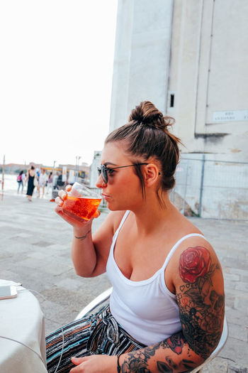 young woman drinking cocktail in venice Italy Venice Venice, Italy Italy Travel Travel Destinations One Person Real People Lifestyles Incidental People Leisure Activity Women Young Adult Day Adult Focus On Foreground Food And Drink Sitting City Hairstyle Young Women Outdoors Drinking Dining Summer Tattoo