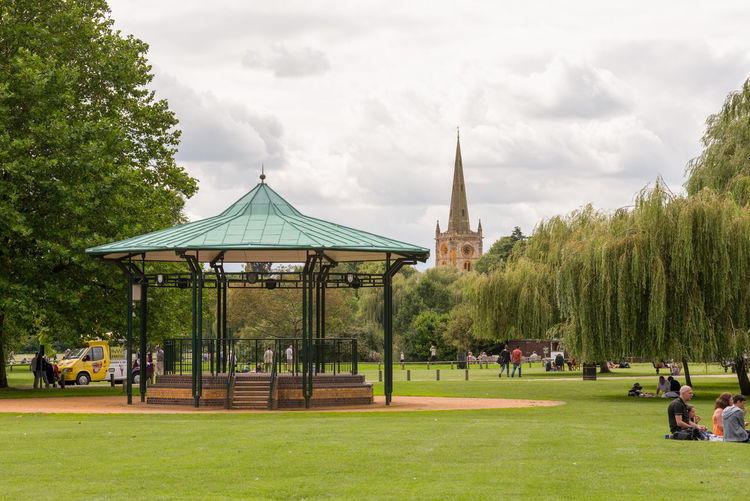A summer time view of the empty Band stand in public Recreation Ground park in Stratford on Avon with the spire of the Holy Trinity Church in the back ground. Architecture Day Grass Green Color Growth Landscape Large Group Of People Nature Outdoors People Sky Tree