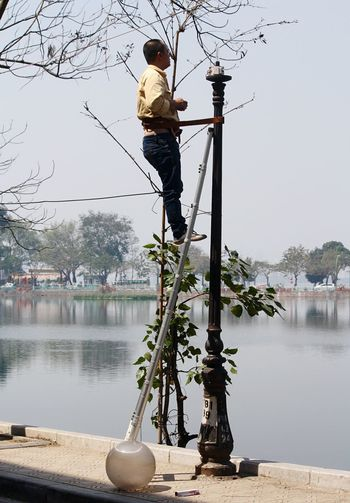 Electrician repairing street light at truc bach lake