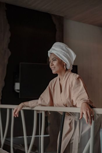 Smiling woman wearing bathrobe and looking away while standing by railing at home