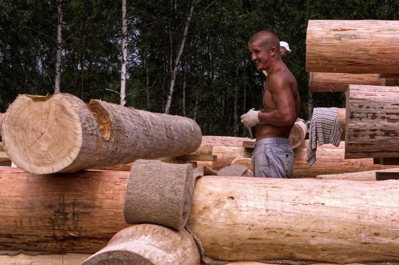 Full length of man working on wooden log