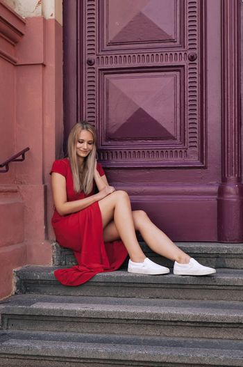 Full length of woman sitting on steps against closed doors
