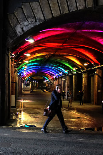 The Arches. On The Phone... Arch Arches Architecture Brick Arch Built Structure Business Man City Full Length Illuminated Leisure Activity Lifestyles Lighting Equipment Men Motion Multi Colored One Person Real People Stone Arch The Way Forward Tunnel Walking