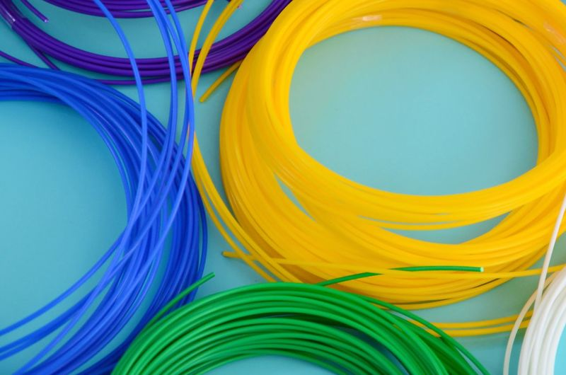 High angle view of multi colored cables over blue background