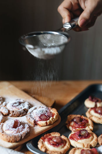 Cropped hand of woman dusting powdered sugar on cookies with strainer on table