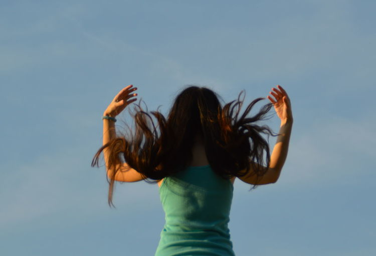 Rear view of young woman with tousled hair against sky