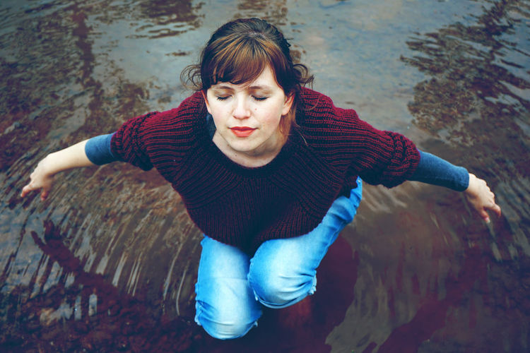 High angle view of young woman with eyes closed crouching in lake