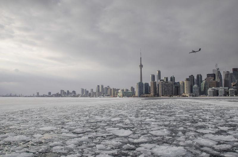 Frozen lake ontario by urban skyline