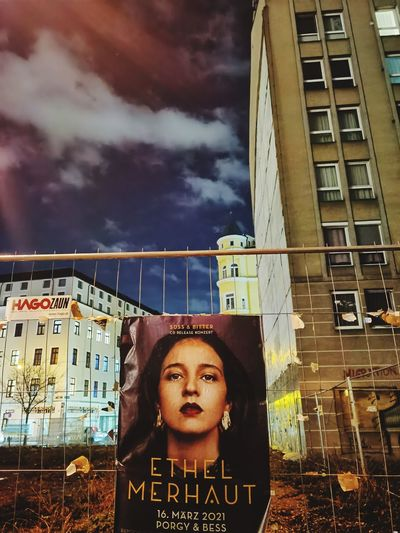 Portrait of young woman against building in city