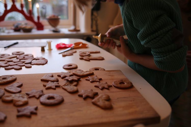 Midsection of girl decorating gingerbread cookies on table
