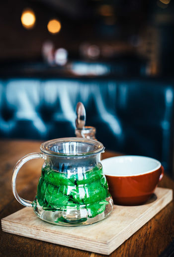 Close-up of mint tea in jar by cup on table