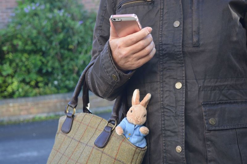 Midsection Of Woman Holding Smart Phone While Standing Outdoors