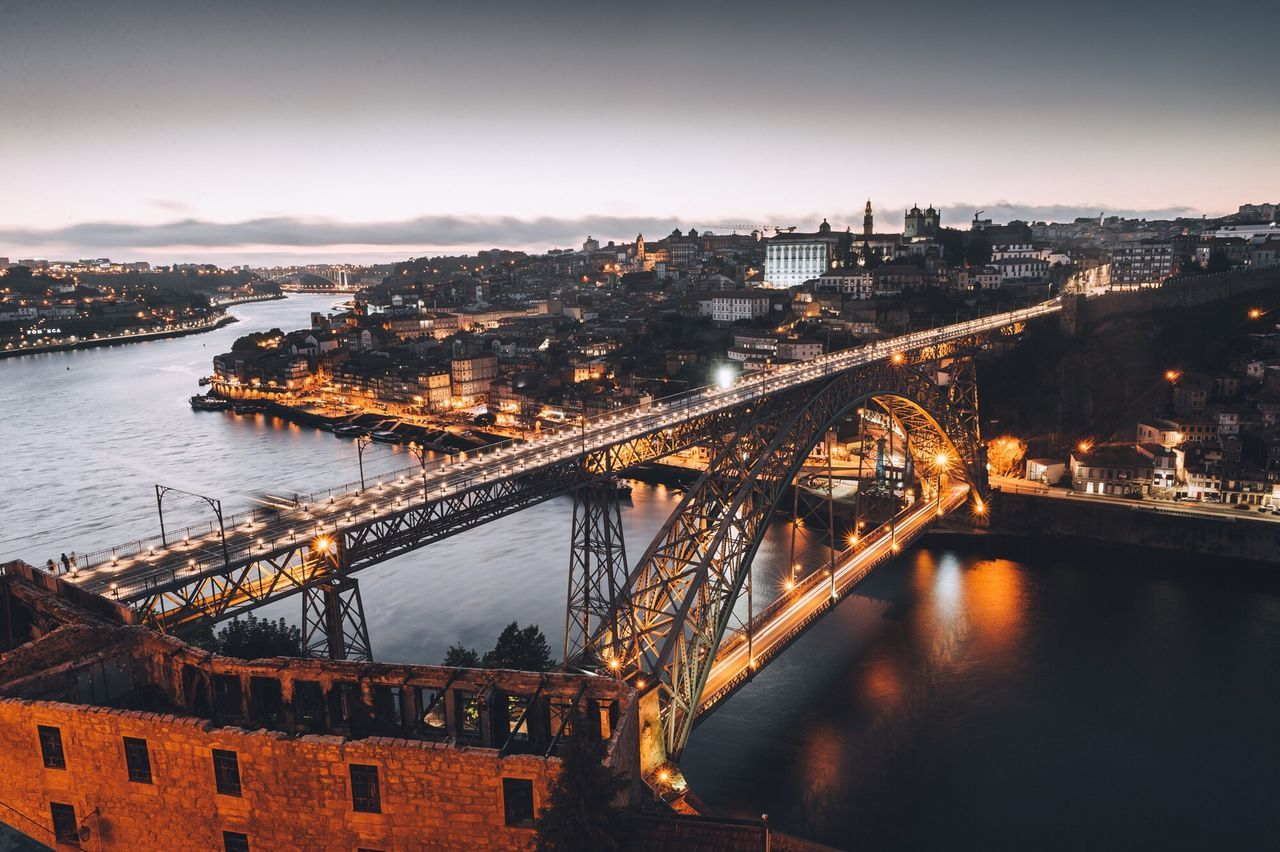 High Angle View Of Bridge Over River In City At Dusk
