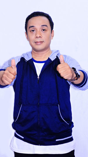 Portrait Young Smile Asian man Front View Looking At Camera One Person Standing Studio Shot Young Men Gesturing Clothing Males  Young Adult Three Quarter Length Casual Clothing Portrait Indoors  White Background Men Lifestyles Waist Up