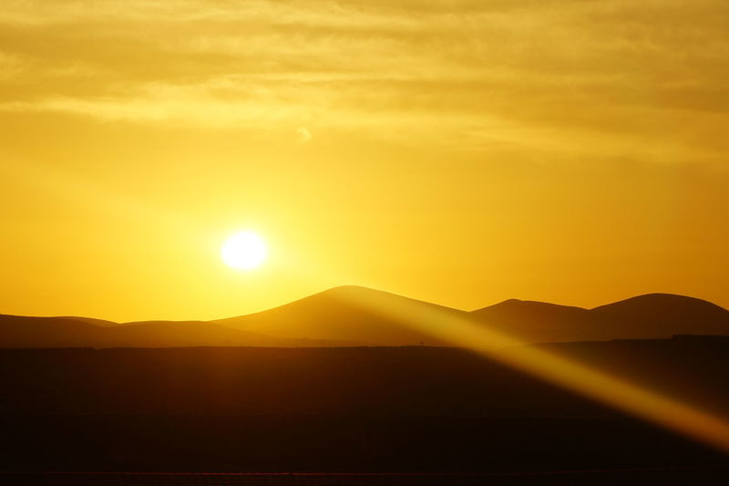 Beauty In Nature Day Desert Landscape Mountain Mountain Range Nature No People Outdoors Scenics Silhouette Sky Sun Sunlight Sunset Tranquil Scene Tranquility Yellow