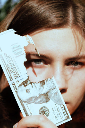 Close-up portrait of teenage girl with burned money