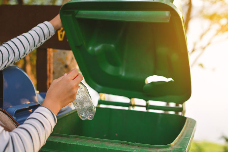 Cropped hands of person throwing bottle in garbage bin
