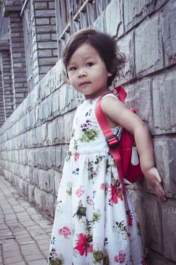 Portrait of cute girl standing against brick wall