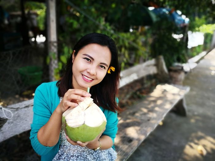 Portrait Of Smiling Woman Having Coconut Water While Sitting On Bench At Footpath