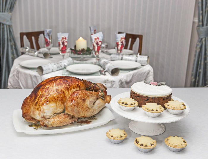 A freshly cooked turkey with mince pies and Christmas cake and a set table in the background. Christmas Cake Mince Pies Seasonal Food Turkey Bird Close-up Cooked Day Food Food And Drink Freshness Indoors  Indulgence No People Plate Ready-to-eat Still Life Sweet Food Table Temptation