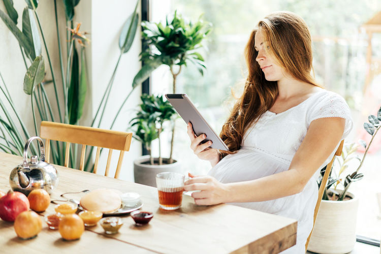 A pregnant woman is eating breakfast at the table and looking into a tablet. communication
