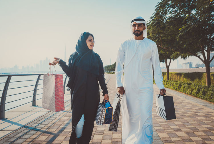 Couple wearing traditional clothing with shopping bags walking on footpath