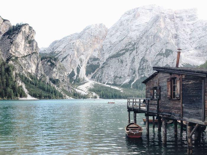 Boat Moored By Stilt Cottage In Pragser Wildsee Against Mountains