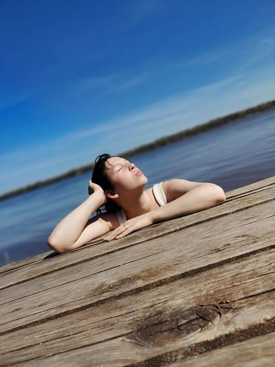 Woman lying on wood against sky