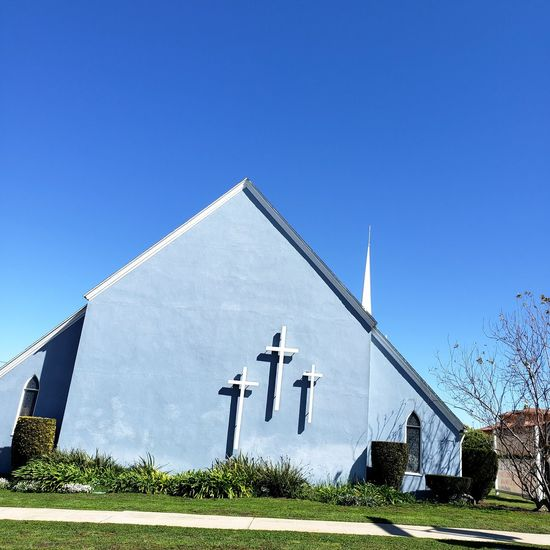 Here is the church, here is the steeple. Open the doors up, see all the people. Grass Sidewalk Drive By Blue Sky Kind Joy Peace Love Steeple White Walls Church Clear Sky Blue Sky Architecture Grass Built Structure Cross Historic Christianity Jesus Christ