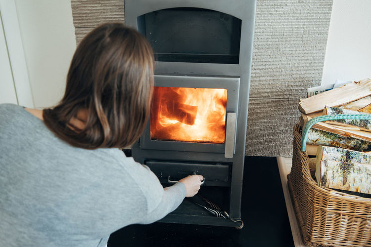 Rear View Of Mid Adult Woman Standing By Fireplace At Home