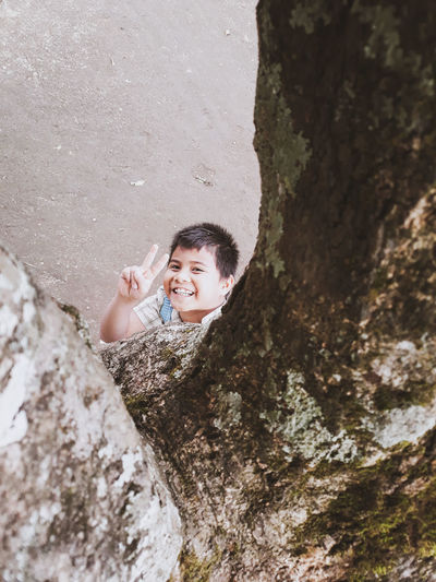 Portrait of smiling boy standing on rock