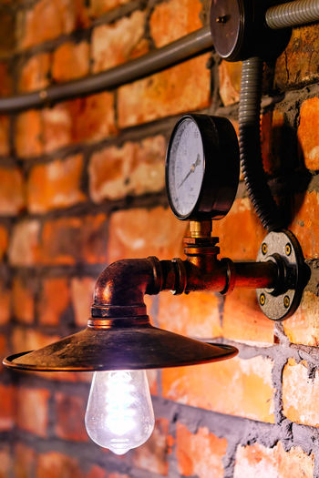 Close-up of electric lamp on brick wall