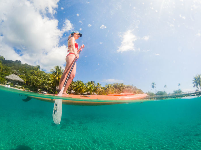 young woman on a SUP in moorea French Polynesia Pacific Travel Cloud - Sky Day Enjoyment Excitement Full Length Lagoon Leisure Activity Lifestyles Motion Nature One Person Outdoors Real People Sea Side View Sky Sup Tahiti Travel Destinations Turquoise Colored Water Young Adult Summer Sports International Women's Day 2019