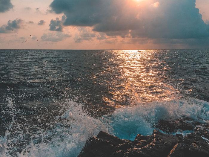 Splashing water of sea against sky during sunset