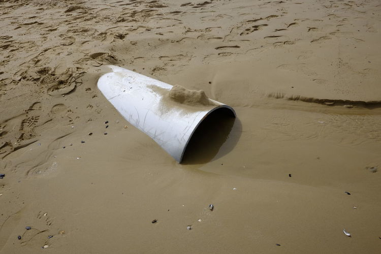 High angle view of pipe in wet sand at beach