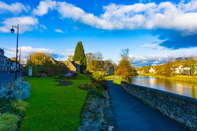 Cityscape of River Kent at Lound Road in Kendal, Cumbria, England in blue sky day Sky Water Cloud - Sky Plant Nature Architecture Tree Built Structure No People Lake Beauty In Nature Tranquility Day Scenics - Nature Building Exterior Park - Man Made Space Outdoors Park