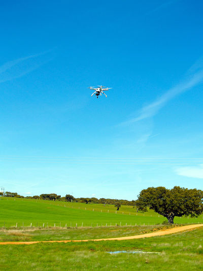 Airplane flying over field against clear blue sky