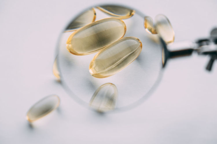 Yellow transparent omega 3 capsules under a magnifying glass. vitamin development concept