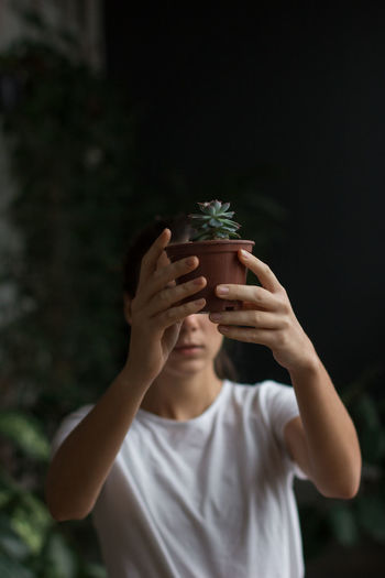 Portrait of young man holding flower pot on potted plant