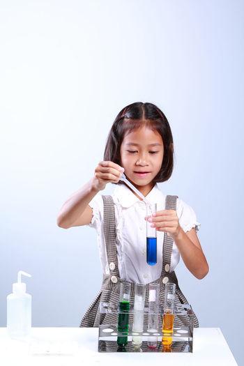 Schoolgirl performing scientific experiment against blue background