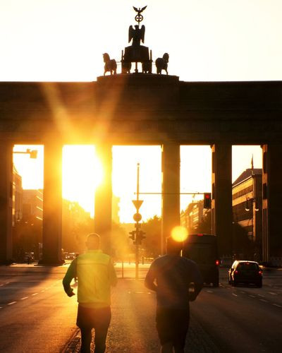 People walking on street in city at sunset