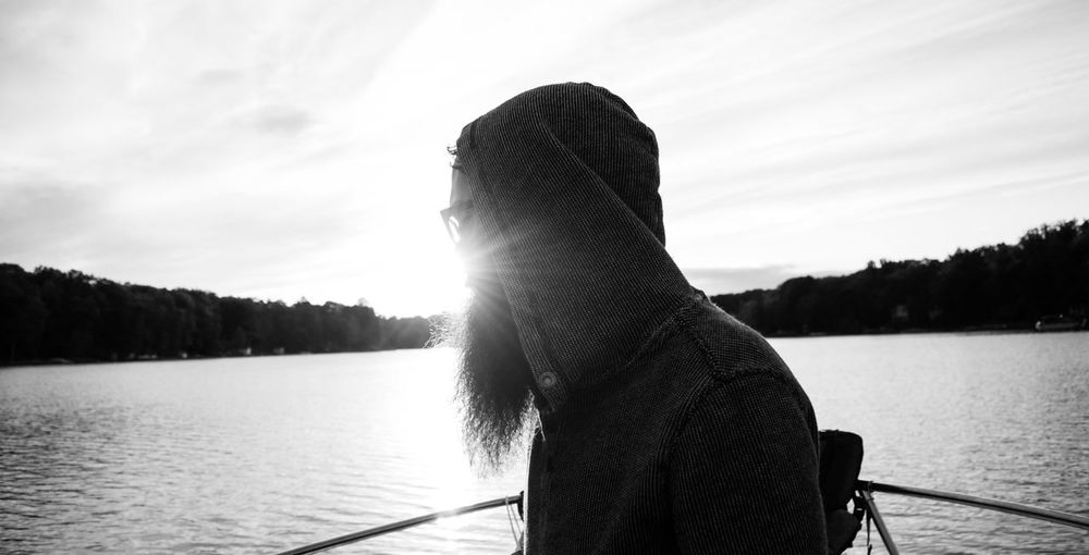 Thoughtful Man Sailing On Boat On River Against Sky During Sunset