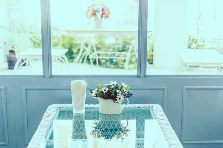 Flowers vase on table against window